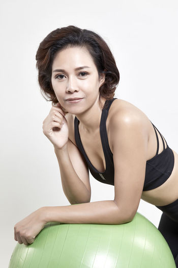 Adult Beautiful Woman Beauty Clothing Exercising Front View Hairstyle Healthy Lifestyle Indoors  Lifestyles Looking At Camera One Person Portrait Sitting Smiling Tank Top Wellbeing Women Young Adult Young Women