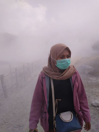 Young woman wearing surgical mask while standing on dirt road in foggy weather