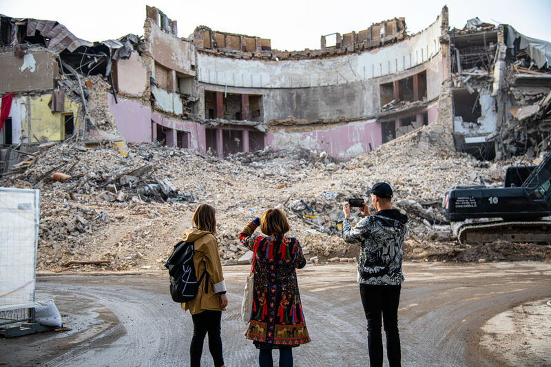 Rear view of people walking in abandoned building