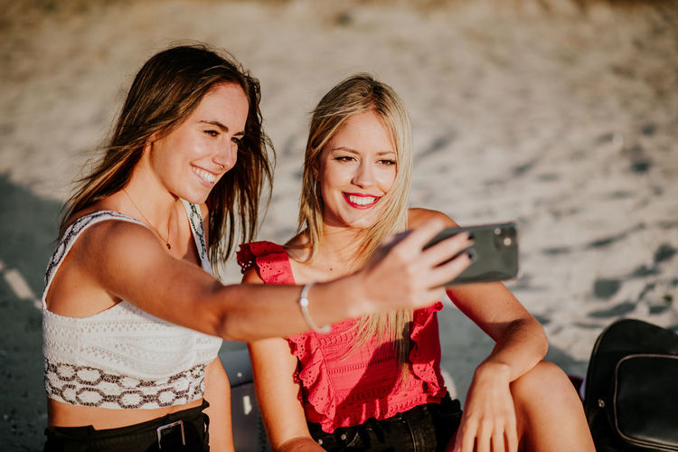 Portrait of smiling young woman using mobile phone
