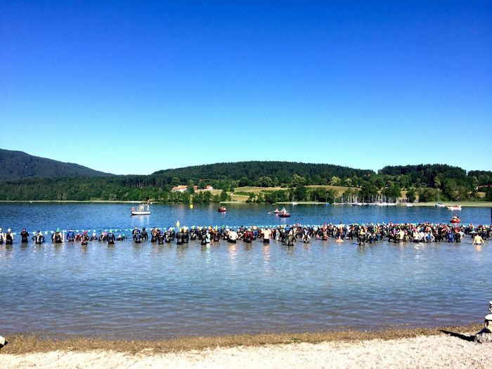 View of swimmers in lake against blue sky