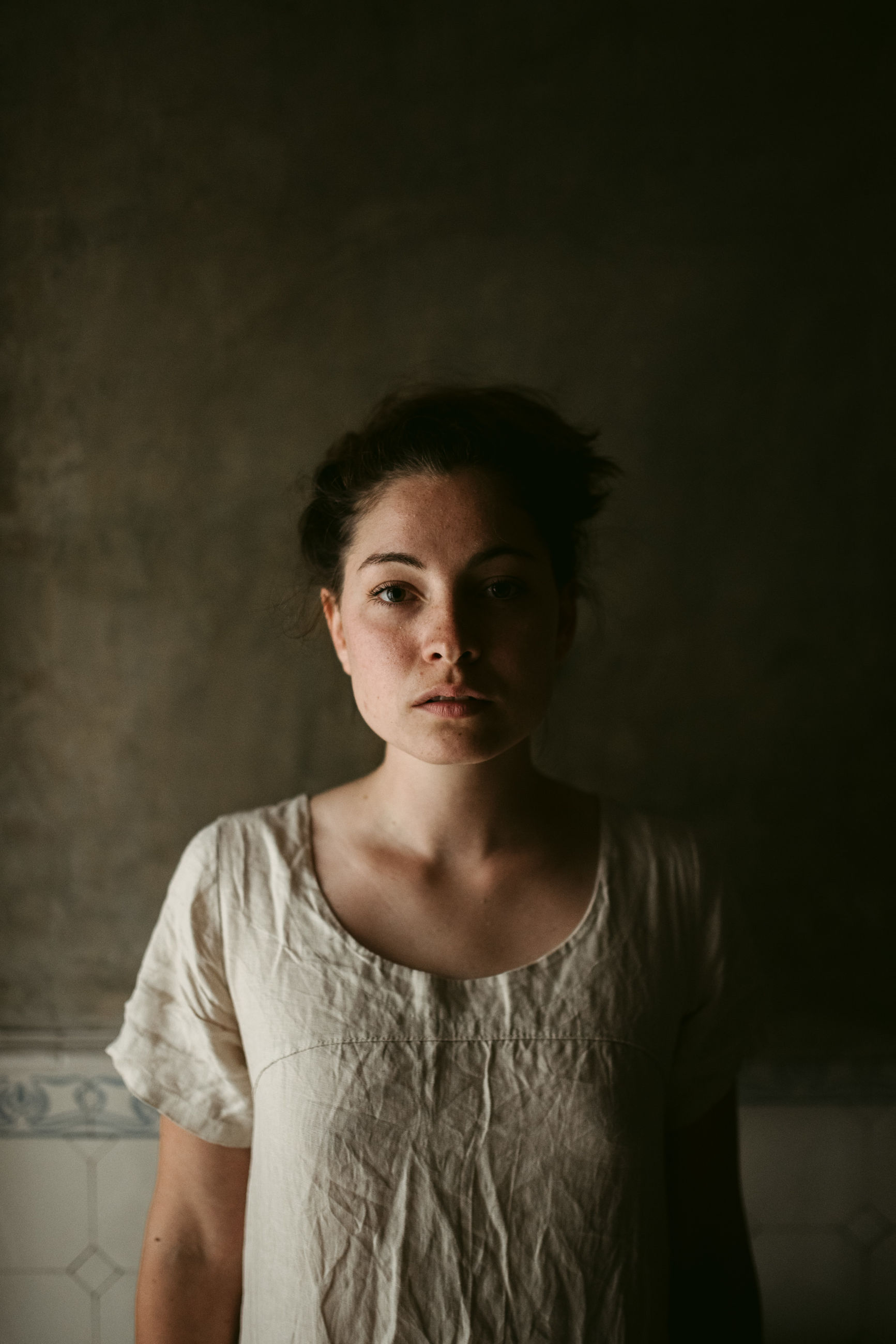 front view, portrait, one person, young adult, looking at camera, indoors, casual clothing, lifestyles, standing, women, real people, young women, waist up, wall - building feature, serious, focus on foreground, adult, hairstyle, contemplation, beautiful woman