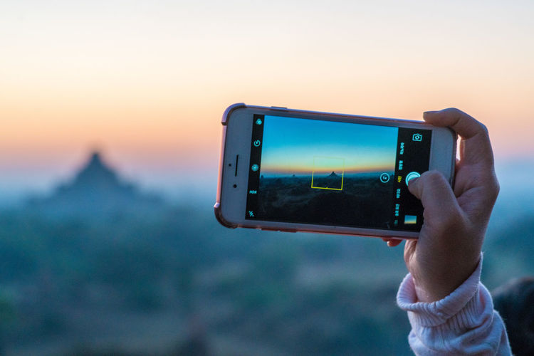 Close-up of person photographing camera on mobile phone