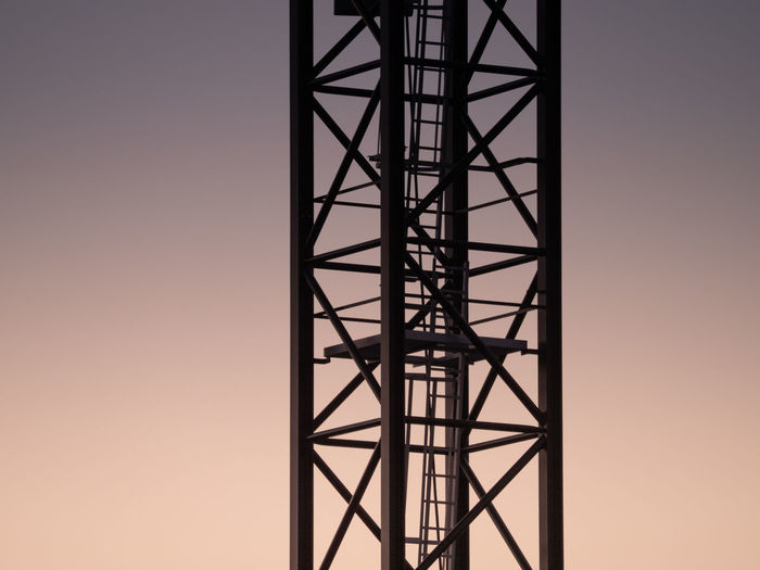 Low angle view of silhouette of metal tower against sky during sunset