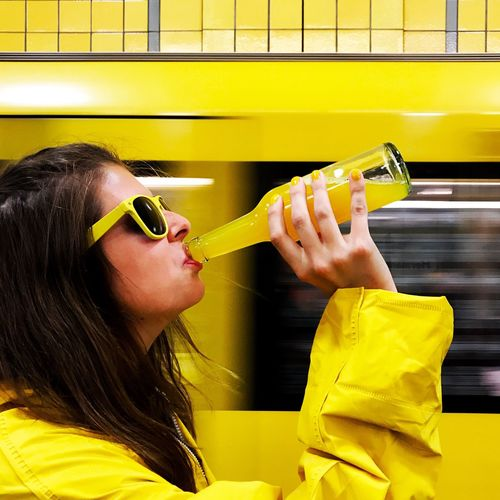 Woman drinking juice against yellow light trail
