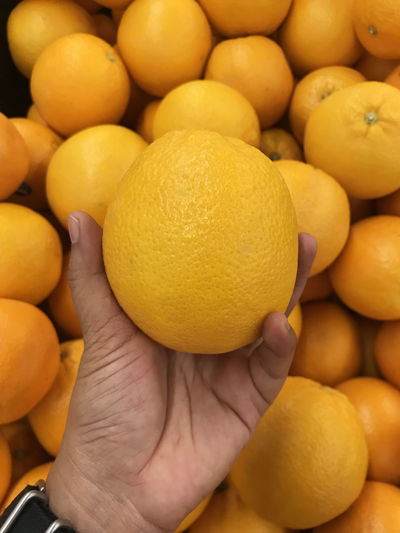 Cropped Hand Holding Lemon At Market