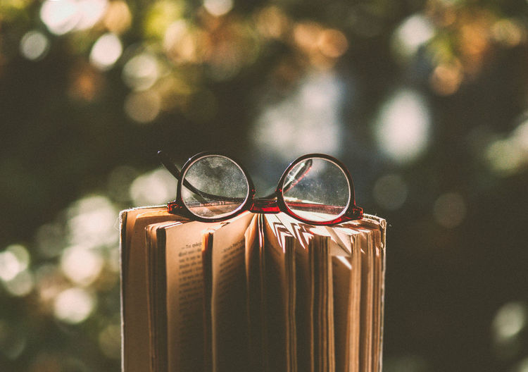Close-up of sunglasses against blurred background, glasses on book, reader