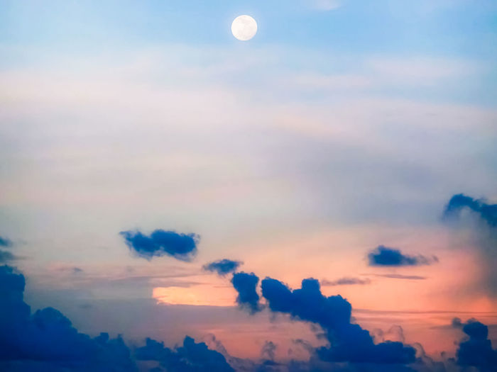 Low angle view of moon in sky at sunset