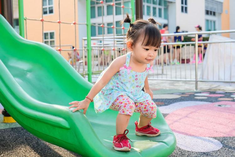 Full length of baby girl standing on slide at park