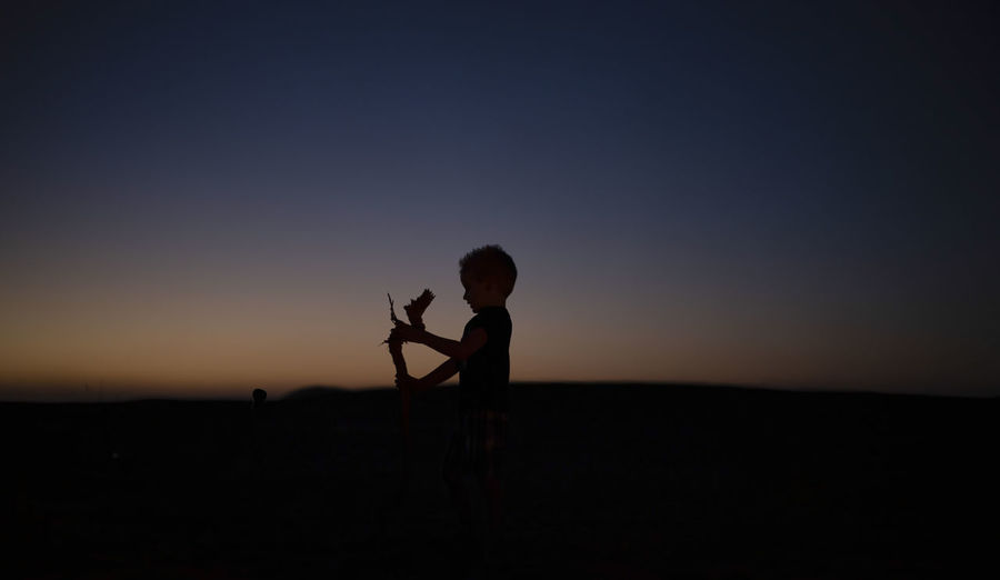Silhouette of child standing against sky during sunset