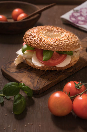 Bagel with tomatoes and Mozzarella Bagel Basil Bread Burger Close-up Cutting Board Day Food Food And Drink Freshness Hamburger Indoors  Meat No People Ready-to-eat Table Tomato Vegetable Wood - Material