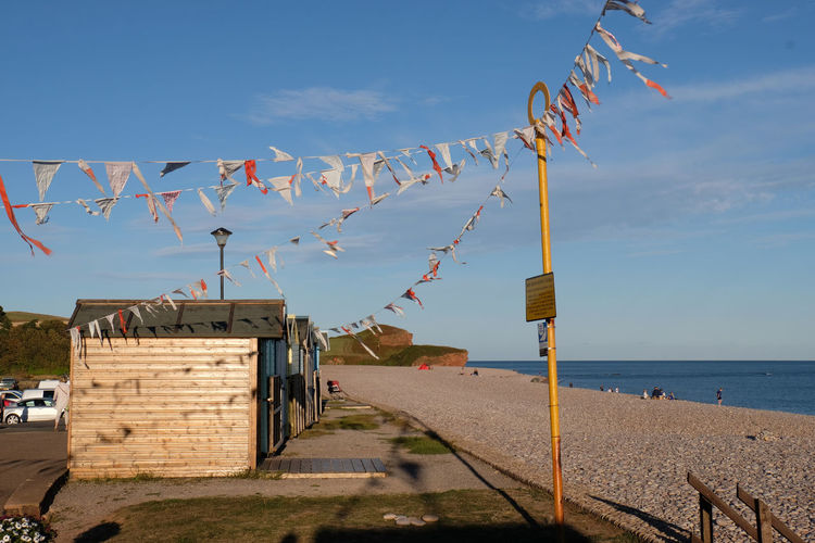 Bunting by the Beach Calming Evening Light Tranquility Atmospheric Mood Beach Beach Hut Built Structure Bunting Bunting Flags Coastal Decoration Evening Sky Hanging Horizon Nautical No People Sea Seaside Holidays Sky Summery Sunlight Tranquil Scene Water Wind