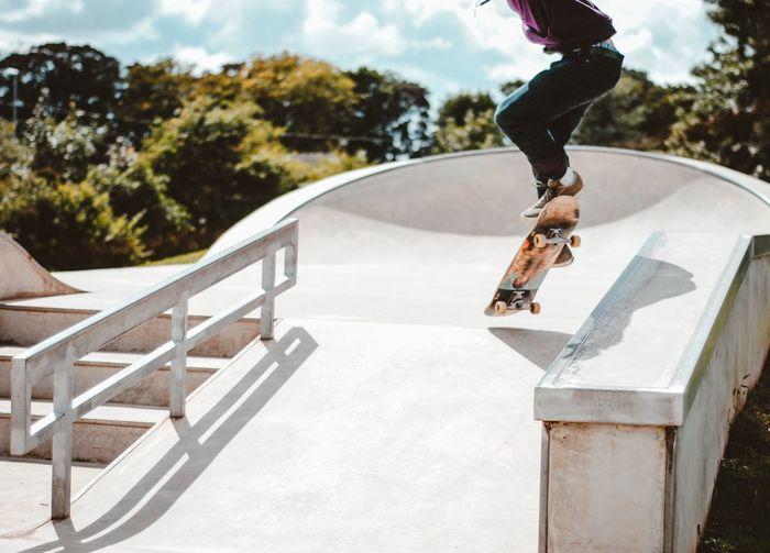 Skateboarder jumping in skatepark