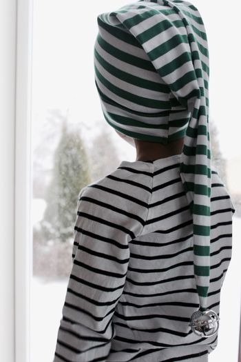 Rear view of child wearing striped santa hat while looking through window at home