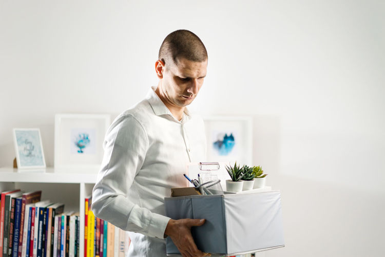 Mid adult man holding container at home