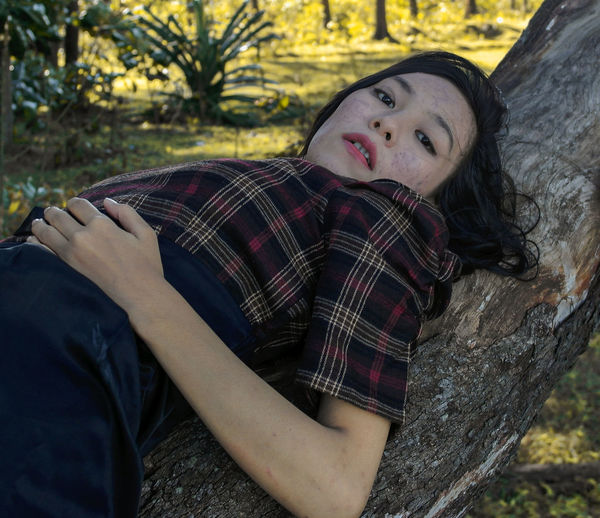 Portrait of young woman lying down on tree trunk
