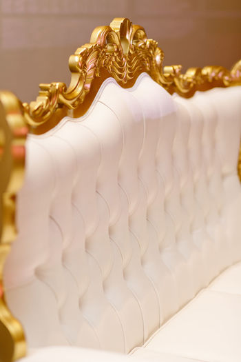Luxury and modern style sofa background with classic white leather texture of an old retro style white buttons Gold Colored No People Indoors  Close-up Art And Craft Focus On Foreground Pattern Creativity Representation Gold Craft White Color Sculpture Still Life Design Selective Focus In A Row Luxury Ornate Wood Frame Leather Sofa Buttons Classic