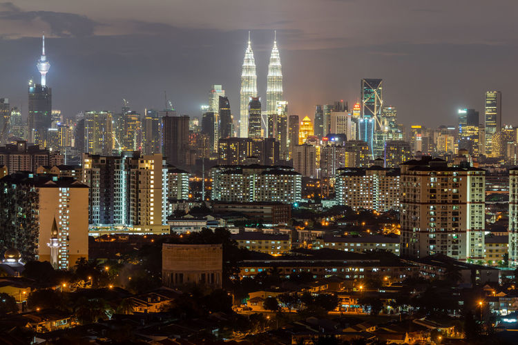 Kuala Lumpur, the capital of Malaysia. Its modern skyline is dominated by the 451m-tall KLCC, a pair of glass-and-steel-clad skyscrapers. Architecture Building Exterior Building Story Built Structure City City Life Cityscape Dark Development Financial District  Glowing Growth Illuminated Modern Night Office Building Outdoors Sky Skyscraper Spire  Tall Tall - High Tower Urban Skyline Wide