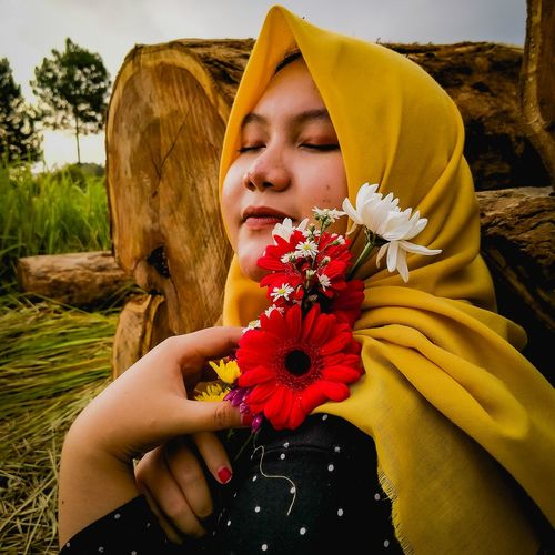Midsection of woman holding yellow flowering plant