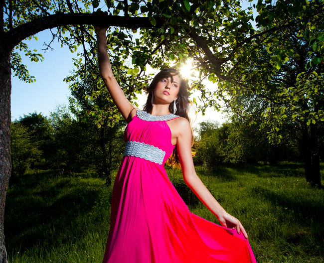 Beautiful woman in a pink summer dress holding on a tree branch One Person Plant Fashion Clothing Young Adult Tree Women Portrait Dress Beautiful Woman Real People Standing Front View Beauty Young Women Adult Looking At Camera Leisure Activity Day Hair Hairstyle Outdoors Human Arm