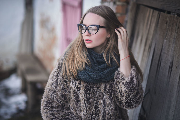 Young woman wearing eyeglasses while standing outdoors
