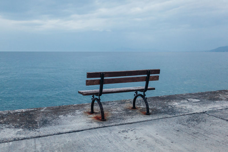 Empty bench on shore by sea against sky