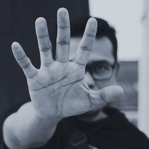 Portrait of man showing stop gesture