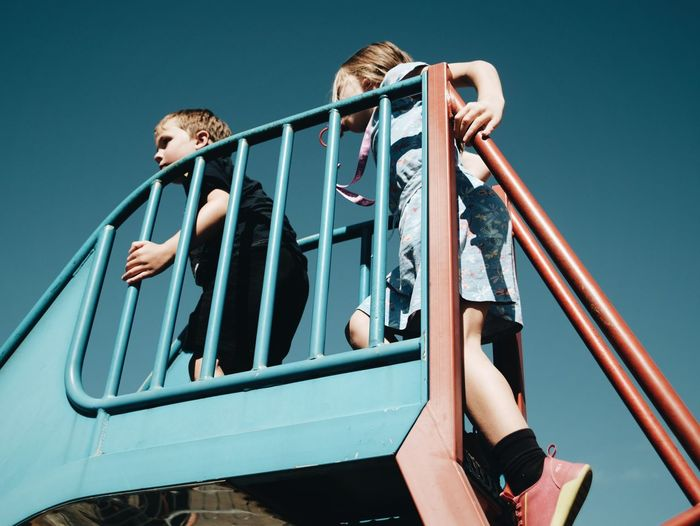 Low angle view of kids on slide against clear blue sky