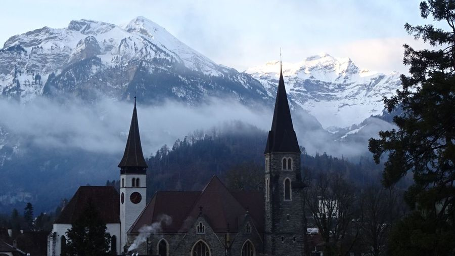 Schlosskirche interlaken by mountain against sky