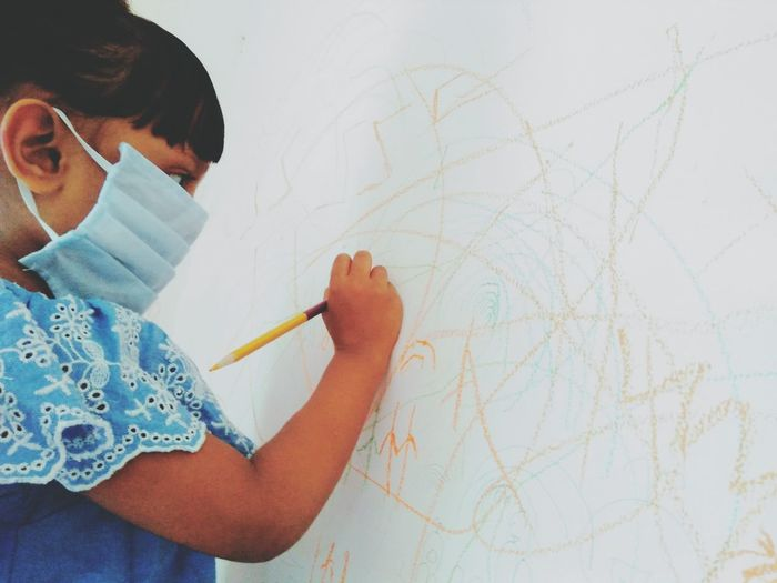 Girl wearing mask drawing on wall