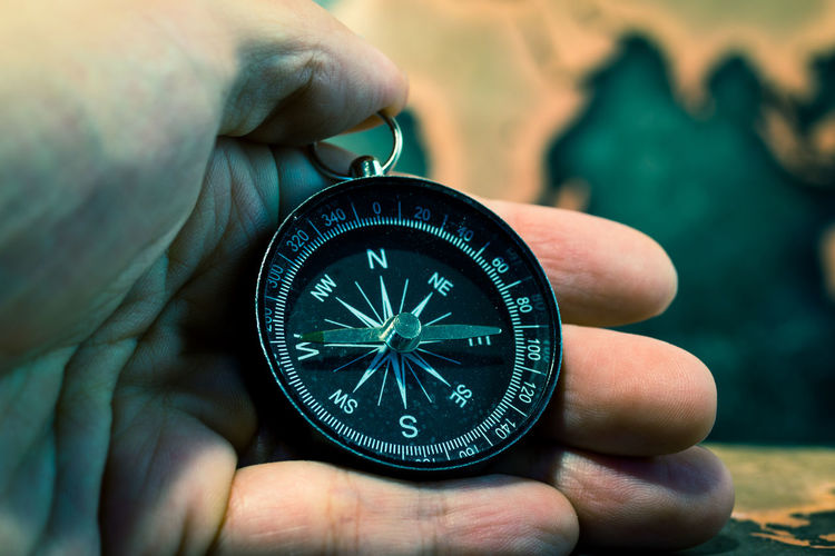 Cropped Image Of Hand Holding Compass