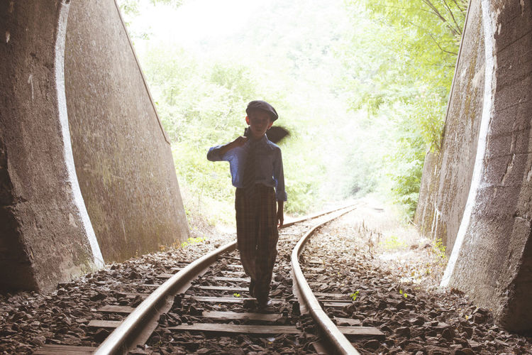 Boy swinging jacket while walking on railroad track in tunnel