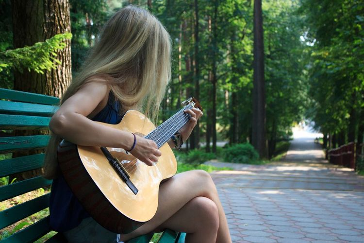 Young woman playing guitar while sitting on bench at park