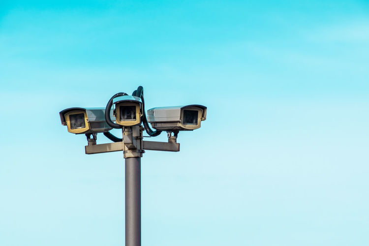 Low angle view of security cameras against blue sky
