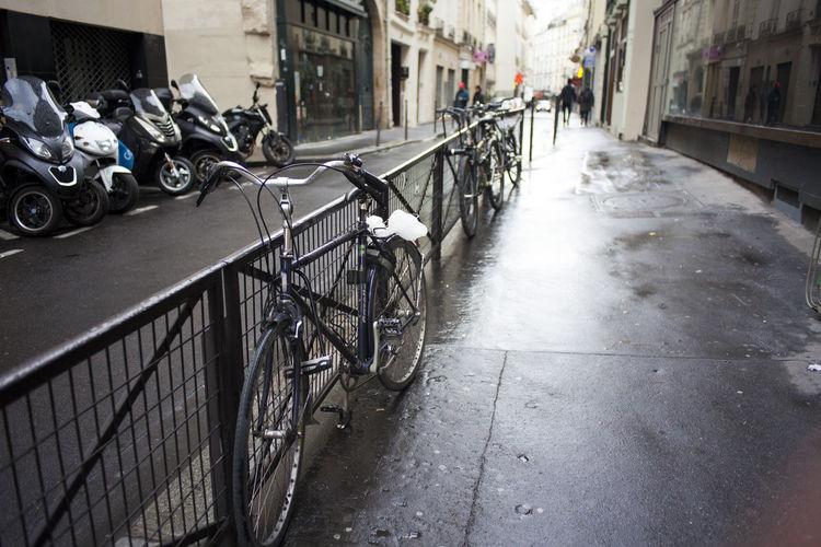 Bicycles on sidewalk by buildings in city
