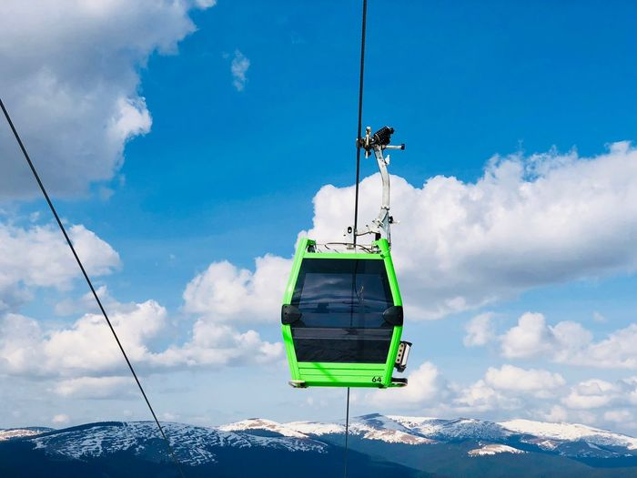 Green gondola lift up in the air over snowcapped mountains on a sunny day with blue sky
