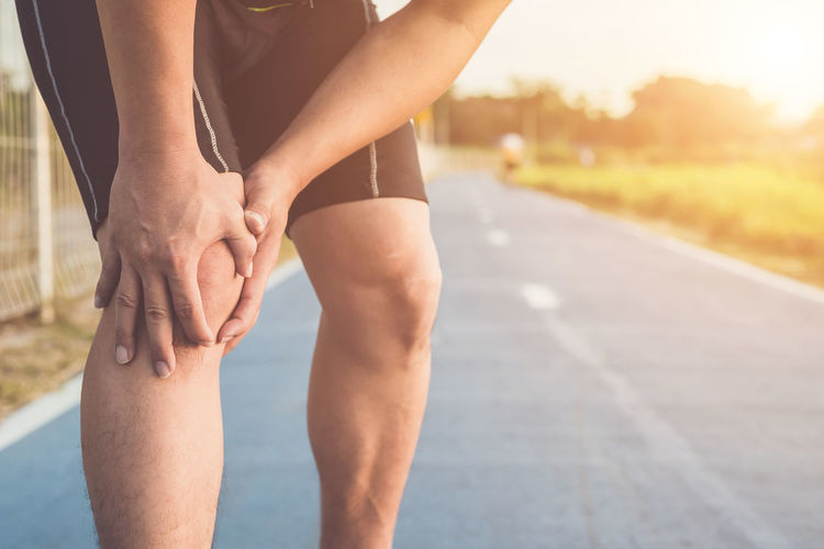 Low section of woman legs on road