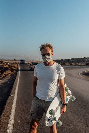 Portrait of man standing on road against clear sky