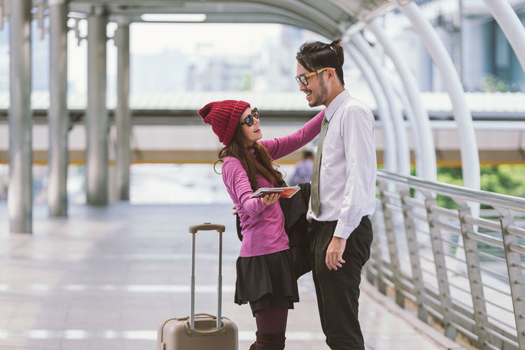 Smiling Couple Standing On Elevated Walkway At Airport