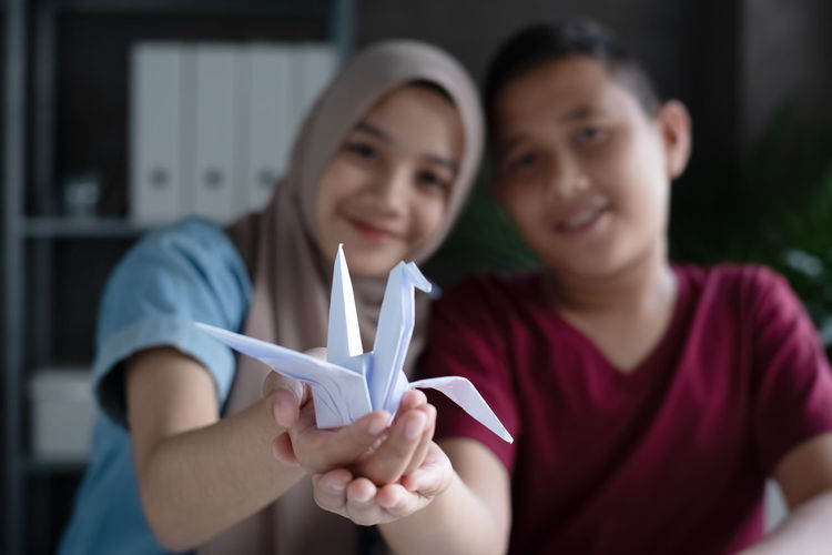 Portrait of smiling siblings holding origami
