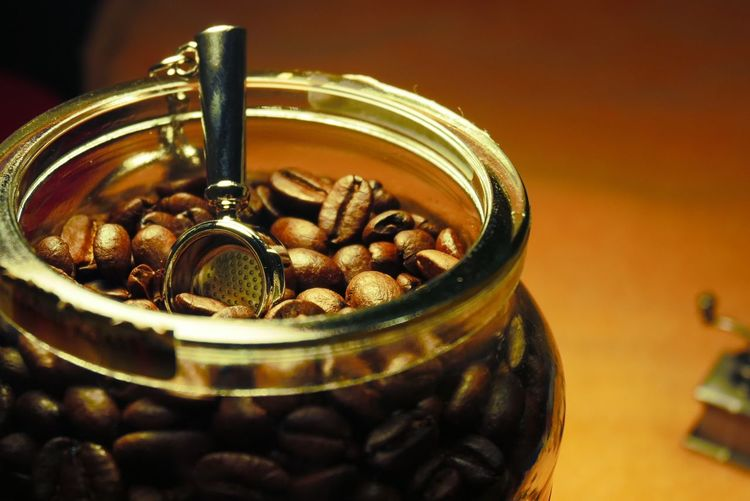 Coffee beans with coffee handle Coffee Handle Food And Drink Still Life Indoors  Food Close-up Table No People Container Freshness Selective Focus Jar Large Group Of Objects Roasted Coffee Bean Healthy Eating Coffee - Drink Metal