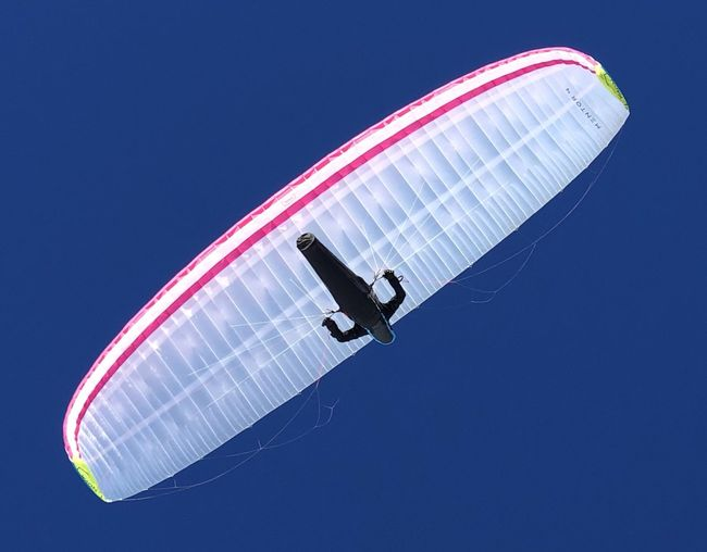 Directly below shot of person paragliding against clear blue sky