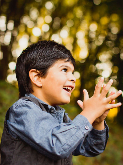 Smiling boy clapping while looking away