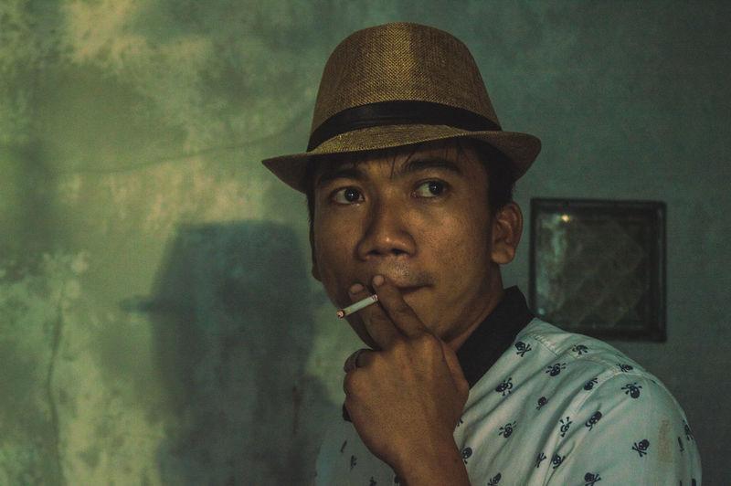 Close-up of man smoking cigarette at home