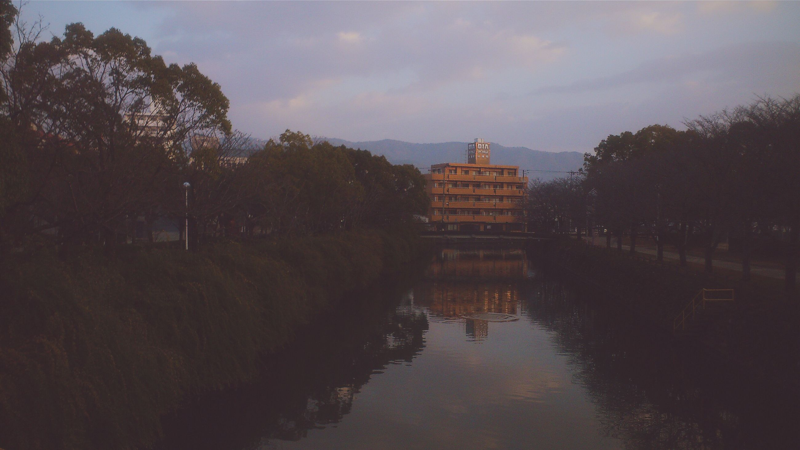 architecture, built structure, building exterior, tree, sky, water, reflection, cloud - sky, waterfront, religion, famous place, place of worship, travel destinations, spirituality, river, tower, history, tourism, dusk, sunset