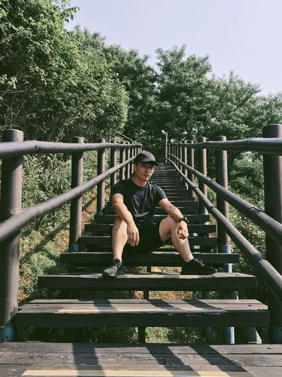 Portrait of young man sitting on railing against trees