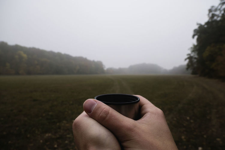 Cropped image of hand holding coffee cup against clear sky