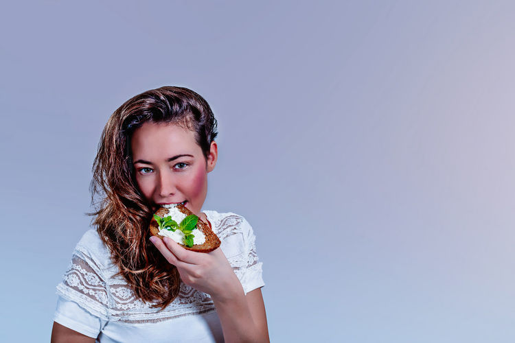 Portrait of beautiful woman eating food against gray background