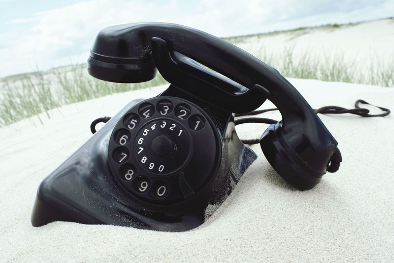 Close-up of retro telephone on sand