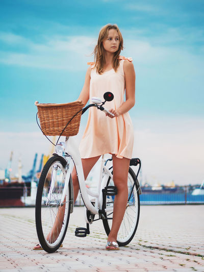 Young woman with bicycle standing on shore against sky